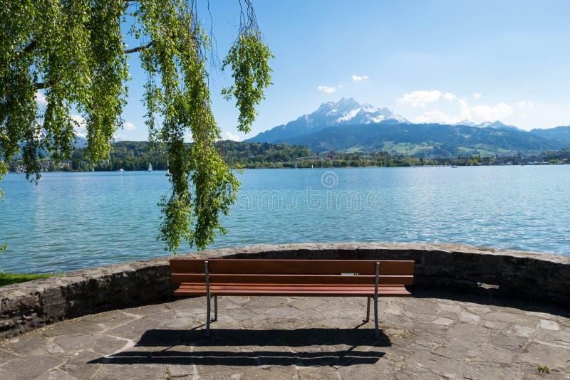 Setzen Sie Gesichter zur Geneva See- und Alpenlandschaftsansicht auf die Bank lizenzfreies stockbild