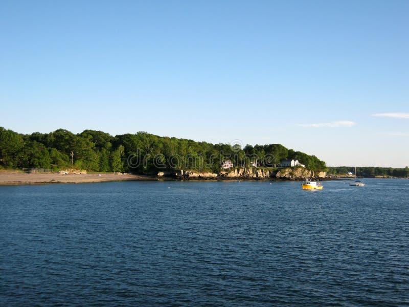 Setzen Sie, Haus auf Inselufer und Boote im Wasser von Portland auf den Strand stockfotos