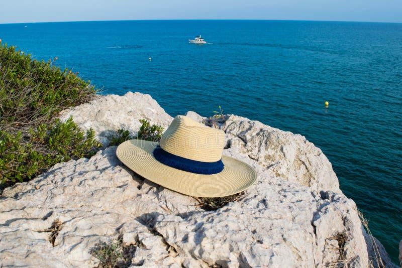 Setzen Sie Hut auf dem Berg und blauen dem Seehintergrund, Sommertag auf den Strand stockbilder