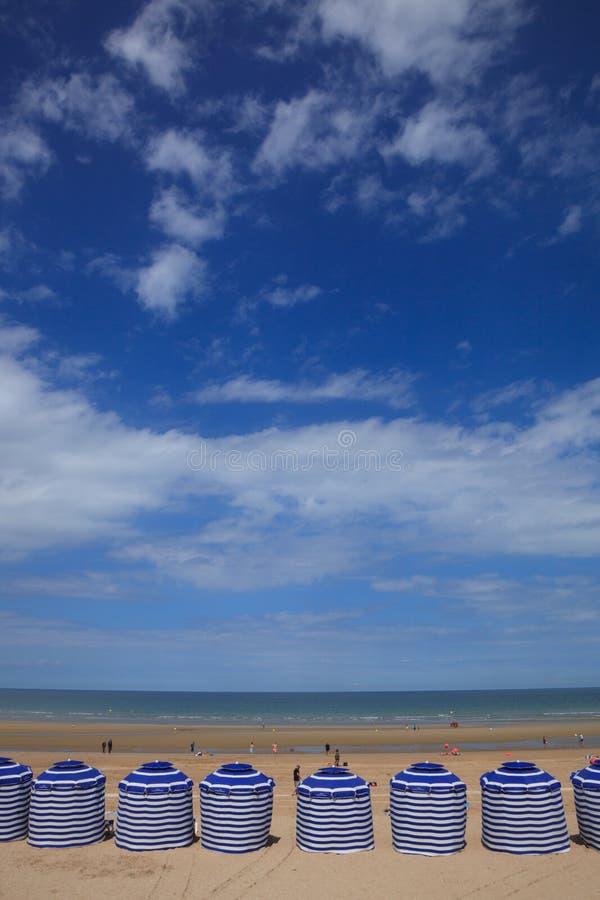 Setzen Sie im Sommer mit Zelten, Sonne und blauem Himmel auf den Strand lizenzfreies stockfoto