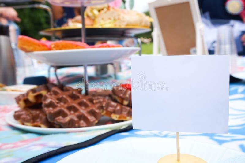 Setzen Sie Karte für einen Gast an einem Teepartypicknick für eine Brautdusche Raum für Kopie auf dem stehenden Namensschild, als stockfoto