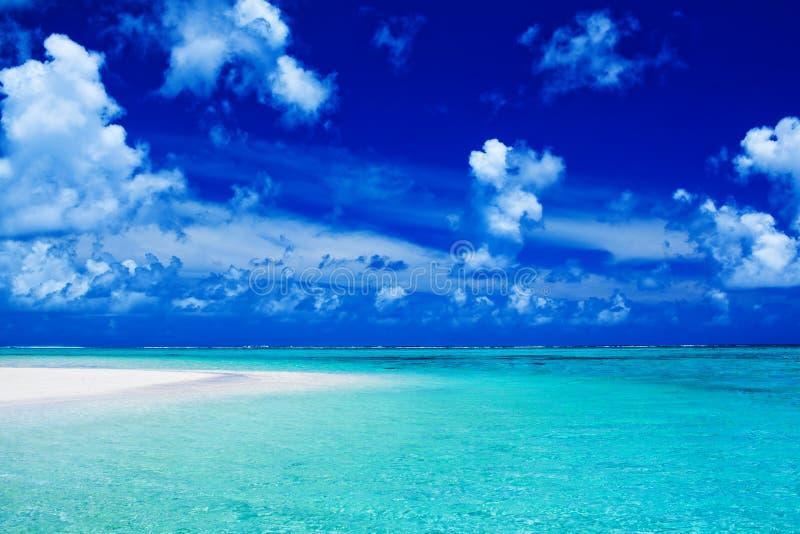 Setzen Sie mit blauem Himmel und vibrierenden Ozeanfarben auf den Strand lizenzfreies stockbild