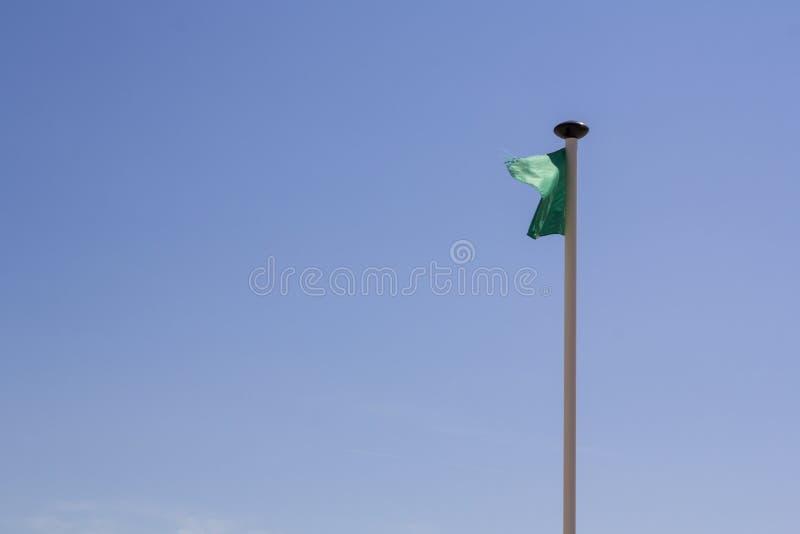 Setzen Sie mit grüner Flagge für sichere Schwimmen gegen blauen Himmel auf den Strand lizenzfreies stockfoto