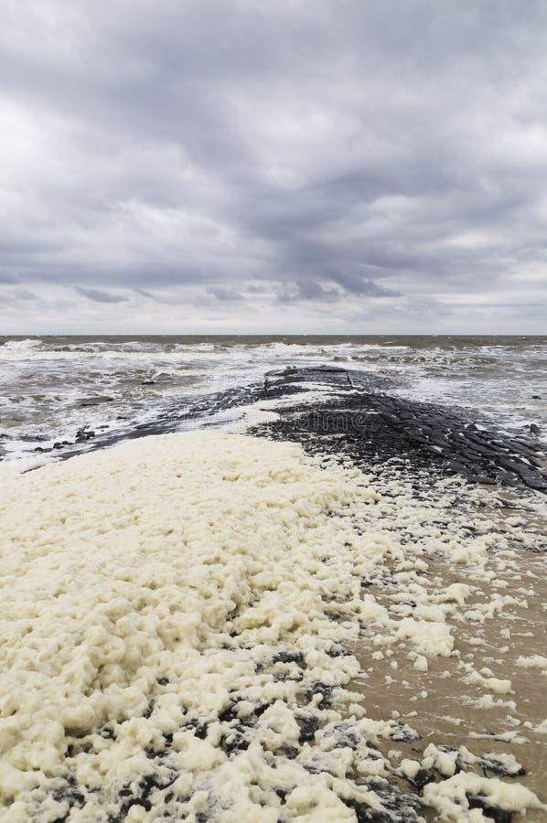 Setzen Sie mit Steinpier und dem Schaum auf den Strand, die durch schweren Sturm verursacht wird stockfotos