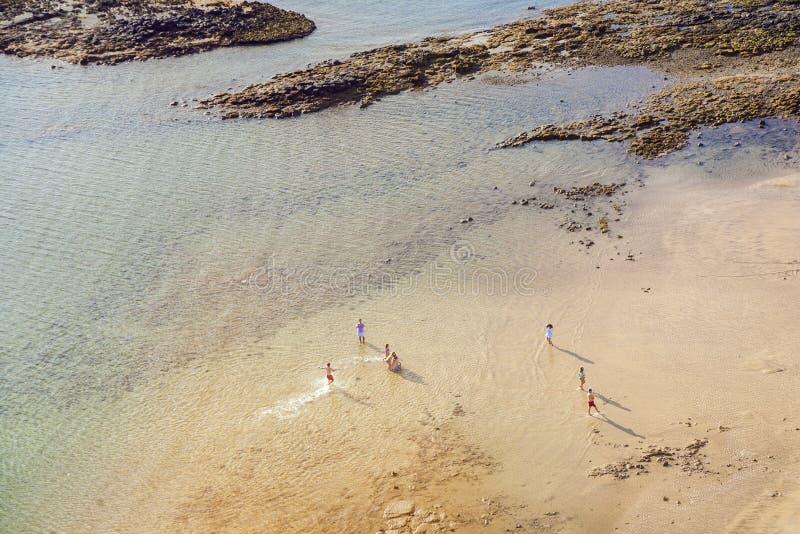 Setzen Sie mit Touristen im Sommer in Arrecife, Spanien auf den Strand stockbilder