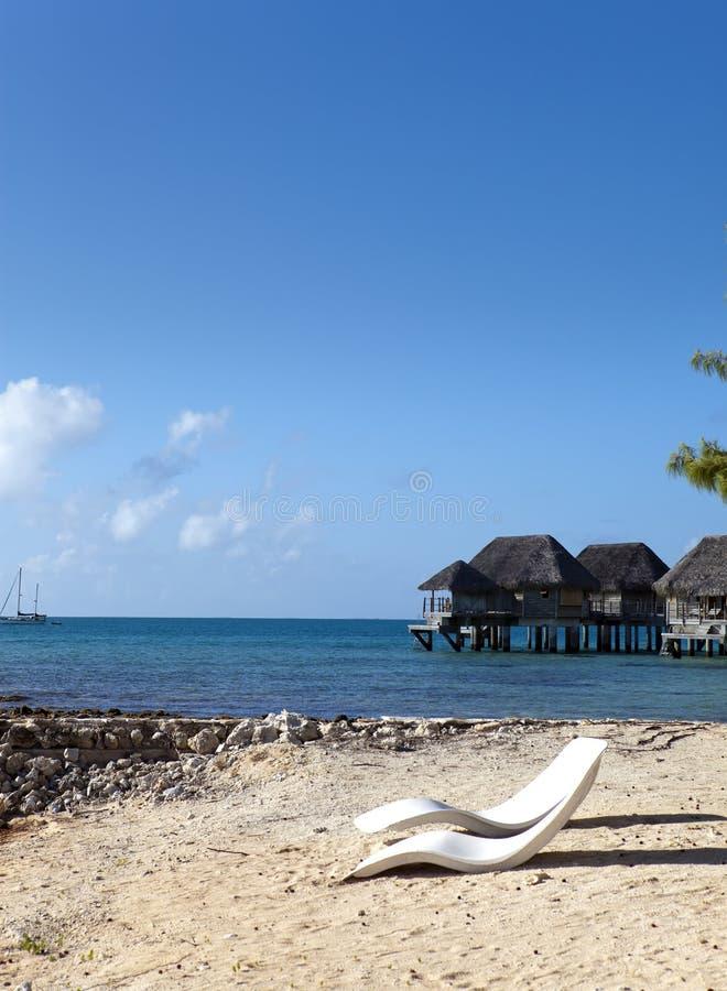 Setzen Sie Sitze auf der sandigen Küste und tropische Häuser im Abstand gegen den blauen Himmel auf den Strand lizenzfreies stockfoto