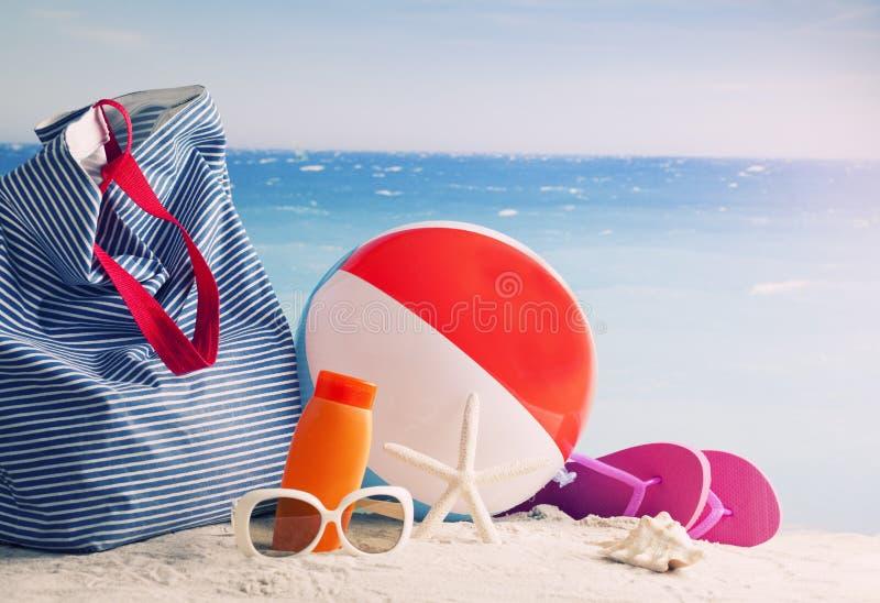 Setzen Sie Tasche, Sonnenbrillen und Flipflops auf einem tropischen Strand auf den Strand stockbild