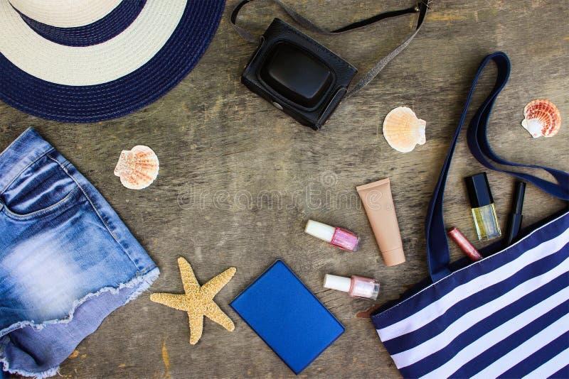 Setzen Sie Tasche, Sonnenhut, Kosmetik, Denimkurze hosen, Kamera, Muscheln auf den Strand stockbild