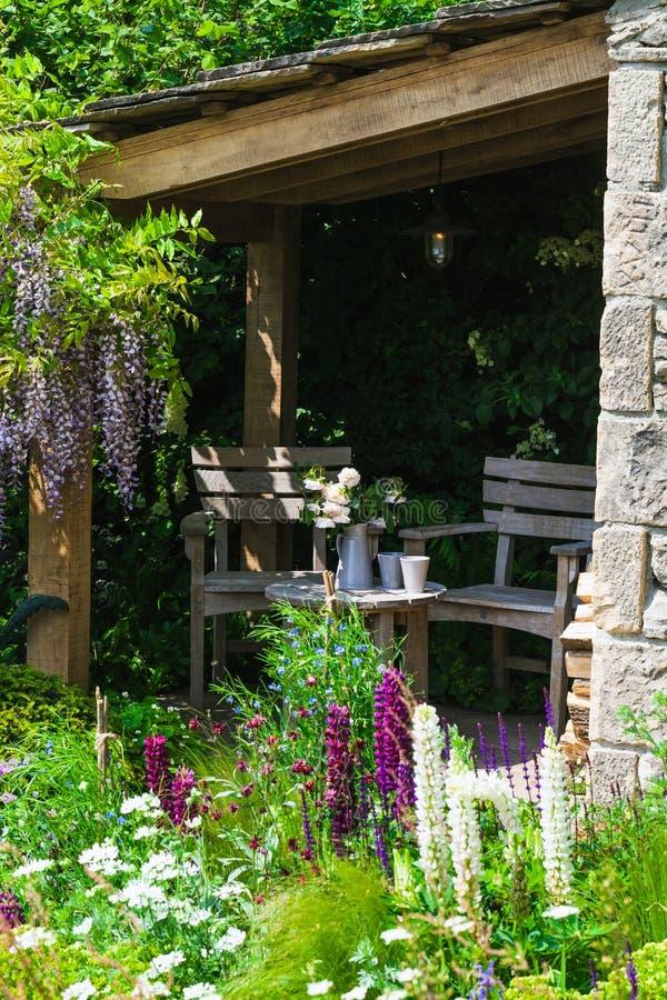 Setzen Sie, um sich in einem schönen Garten zu entspannen stockbilder