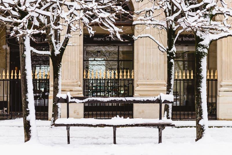 Setzen Sie unter dem Schnee in Paris, Frankreich auf die Bank lizenzfreies stockbild