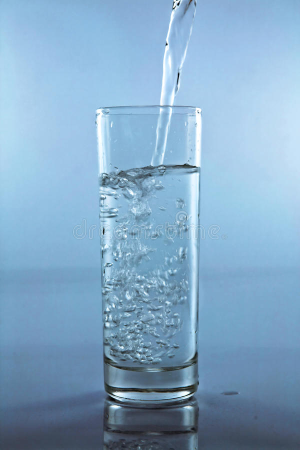 Setzen Sie Wasser in ein Cup lizenzfreie stockbilder
