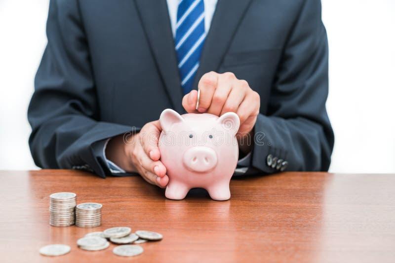 Setzen von Münzen in piggy Bank-Dkonzept von Einsparungen lizenzfreies stockfoto