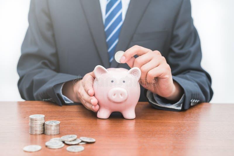 Setzen von Münzen in piggy Bank-Dkonzept von Einsparungen stockfotografie