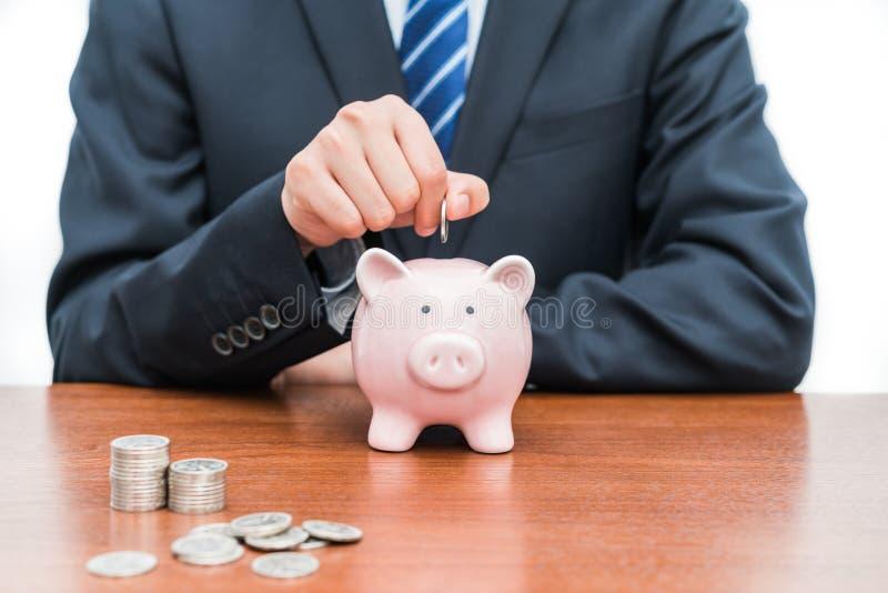 Setzen von Münzen in piggy Bank-Dkonzept von Einsparungen lizenzfreies stockbild