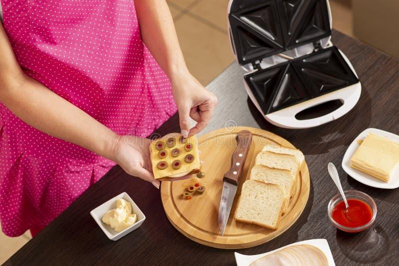 Setzen von Oliven auf ein Sandwich lizenzfreies stockfoto