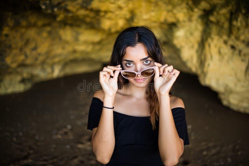 Setzt tragendes Sonnenbrillelächeln der glücklichen schönen mexikanischen Frau nahe auf Felsen auf Sommerberufungszeit auf den St lizenzfreies stockbild