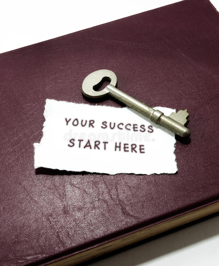 Seu começo do sucesso aqui com chave no livro foto de stock