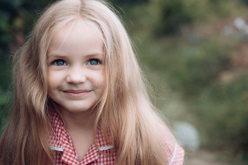 Seu fácil fazer-me feliz Menina pequena com cabelo louro Cabelo longo do desgaste da menina Criança pequena feliz com adorável imagens de stock