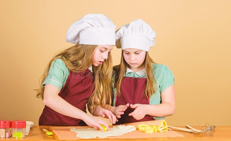 Seu n?o os deuses que cozem potenci?metros Crian?as pequenas que rolam a pasta para cozer tortas As meninas ador?veis que prepara imagens de stock