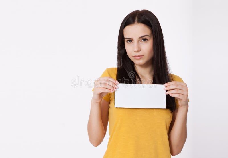 Seu texto aqui Jovem mulher bonita que guarda a placa vazia vazia Retrato do estúdio no fundo branco Modelo para o projeto fotografia de stock