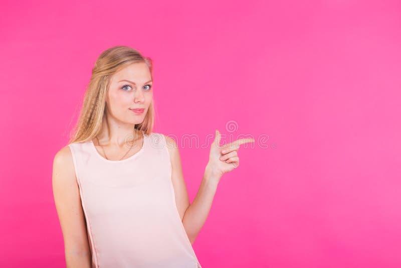 Seu texto aqui Retrato da mulher de sorriso nova que aponta o espaço da cópia Fundo cor-de-rosa fotografia de stock royalty free