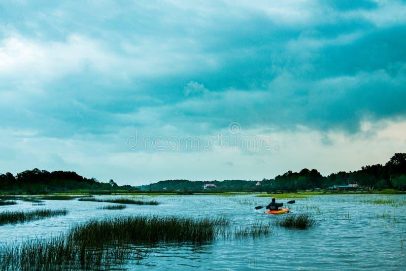 Seul canoë-kayak d'homme dans le lac extérieur du marais de la Caroline du Sud avec le ciel nuageux de dramatica photos libres de droits