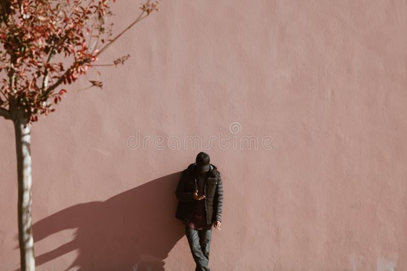 Seul homme avec le chapeau - regardant son mur intelligent de téléphone - l'espace de copie - ombre dure de jour ensoleillé photographie stock libre de droits