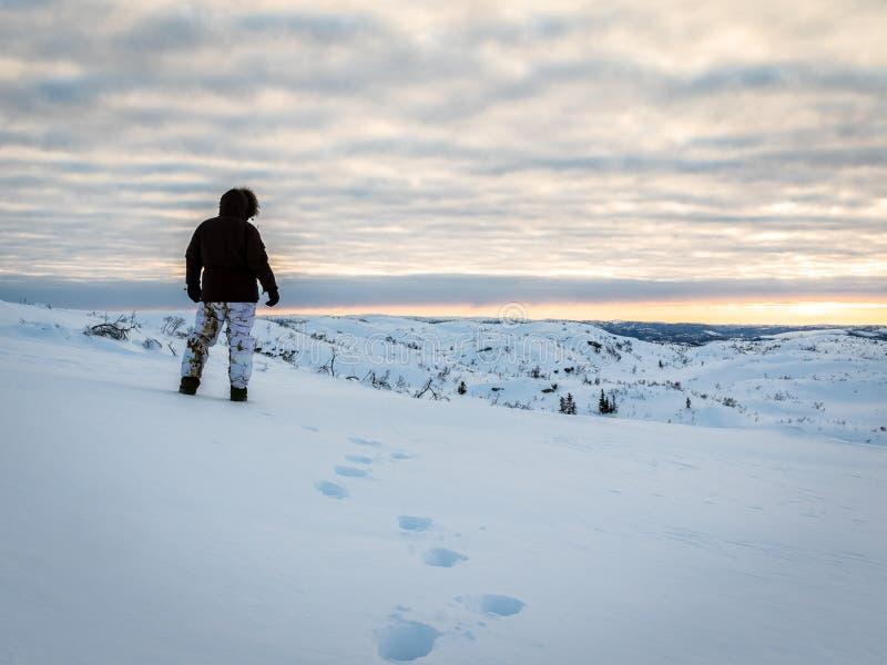 Seul homme marchant dans la neige dans la région sauvage au lever de soleil photographie stock libre de droits