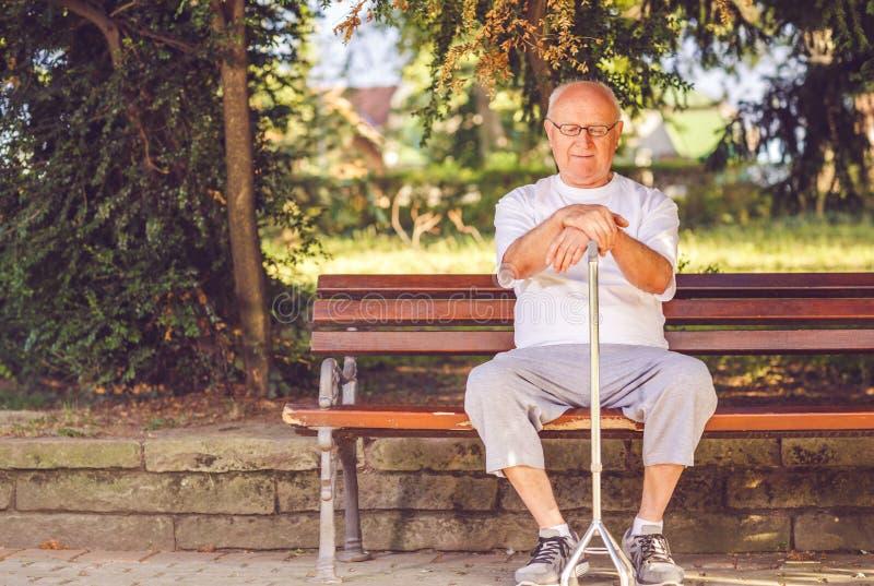 Seul homme plus âgé avec son bâton de marche se reposant sur le banc image stock