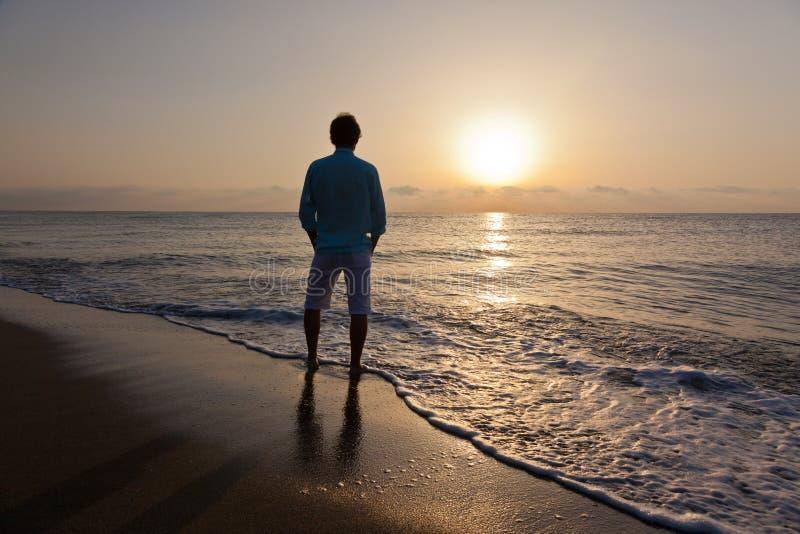 Seul homme sur la plage observant le coucher du soleil photo stock