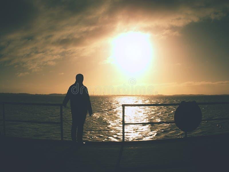 Seul l'homme restent sur le pont de mer et observent le lever de soleil étonnant photo libre de droits