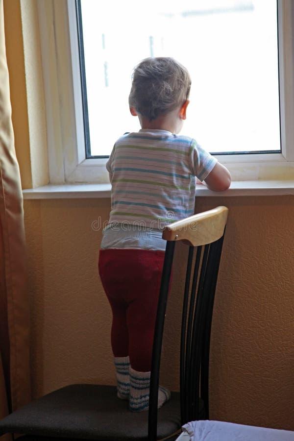 Seul petit garçon regardant dans la fenêtre photographie stock