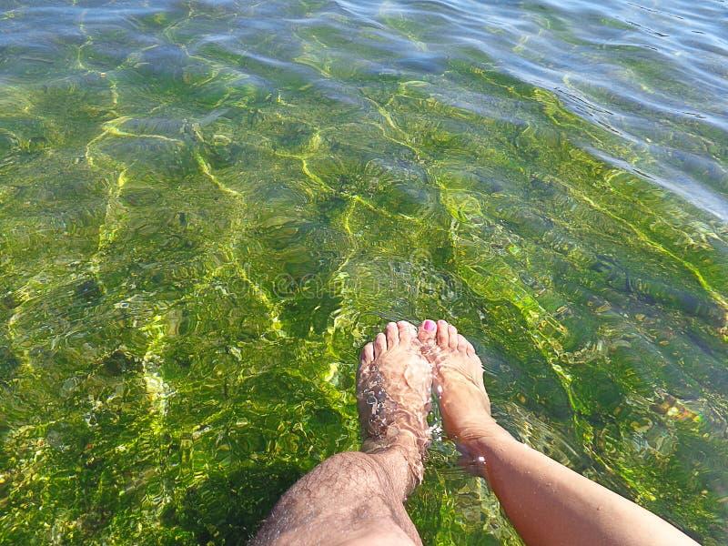Seul pied d'un homme et seul pied d'une femme en eau de mer peu profonde verte clair comme de l'eau de roche avec l'espace pour l image stock