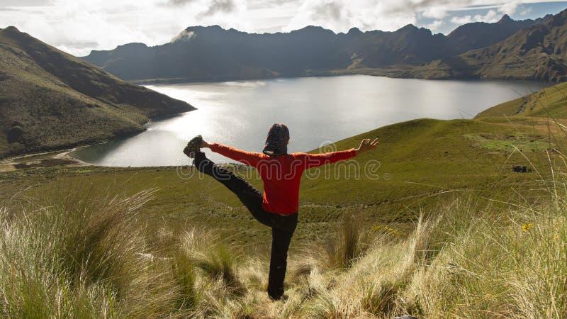 Seul yoga de pratique concentré de jeune femme de Latina devant la lagune de Mojanda images stock