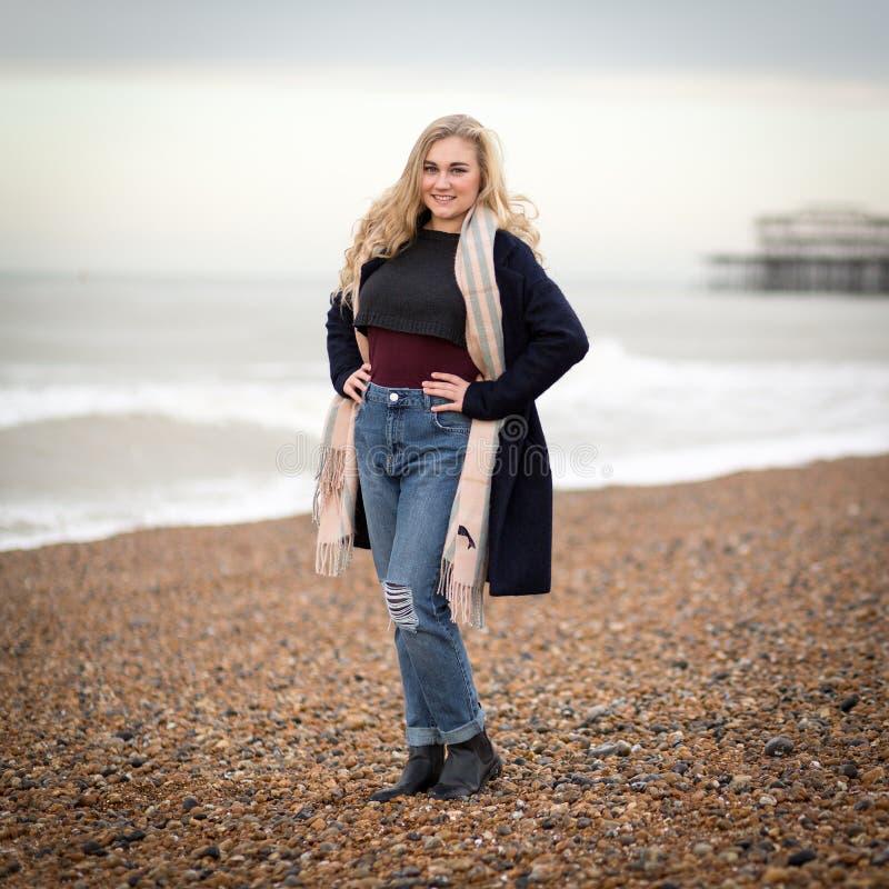 Seule adolescente blonde sûre sur une plage froide photo stock