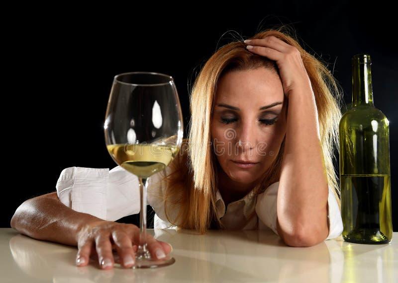 Seule femme blonde alcoolique ivre dans la gueule de bois de souffrance potable déprimée gaspillée en verre de vin blanc photos stock