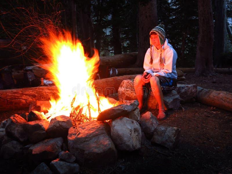 Seule fille par le feu de camp tout en campant photographie stock