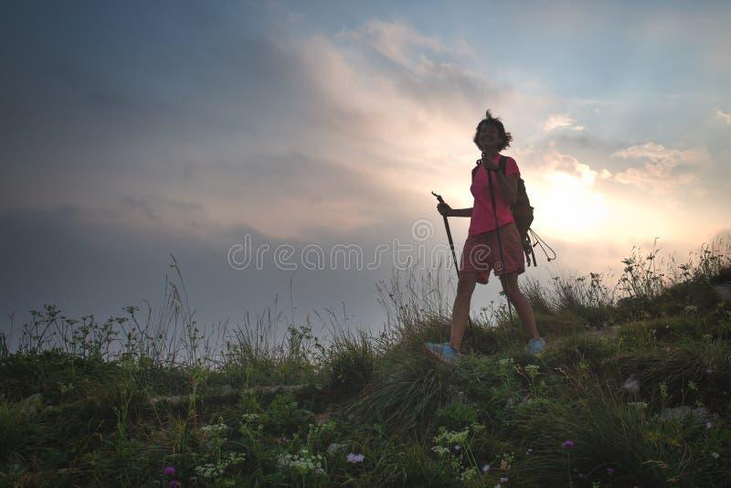 Seule la fille dans les collines marche dans les prés photo stock