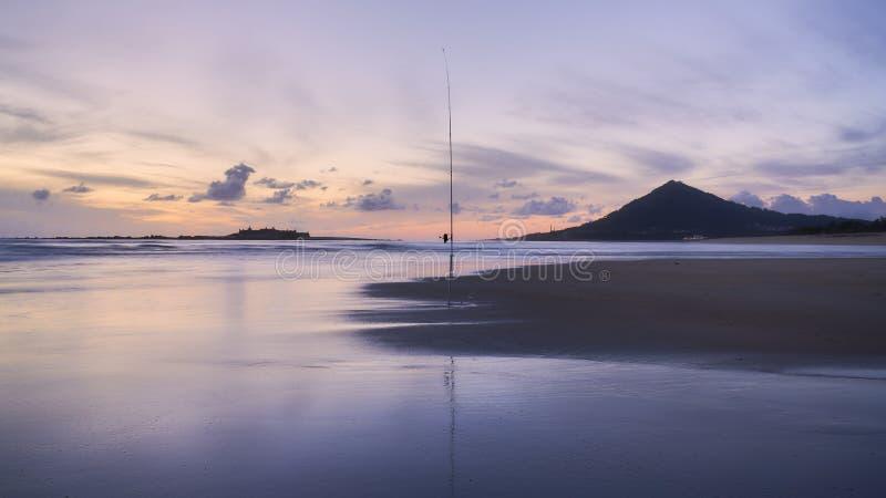 Seule pêche sur le coucher du soleil de plage image stock