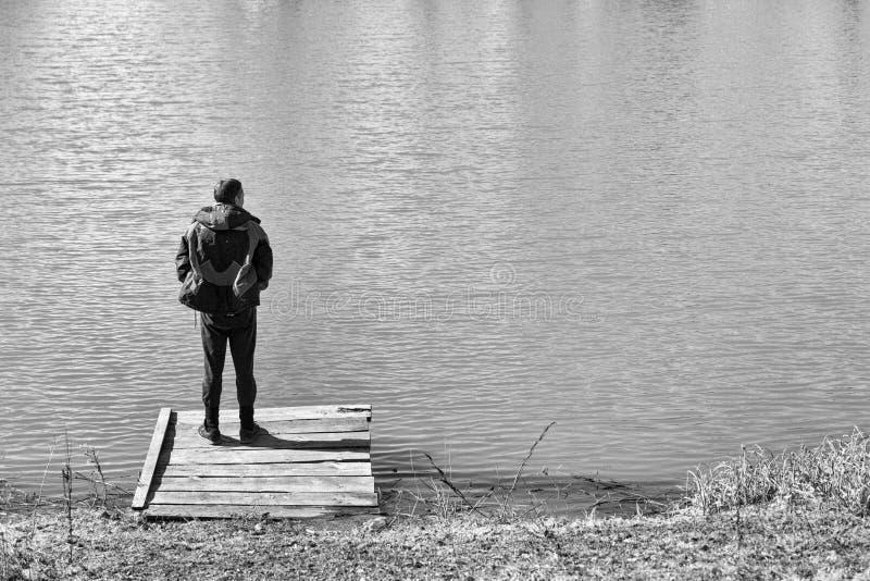 Seule position d'homme sur le bord et regarder fixement le lac Vue arri?re photo stock