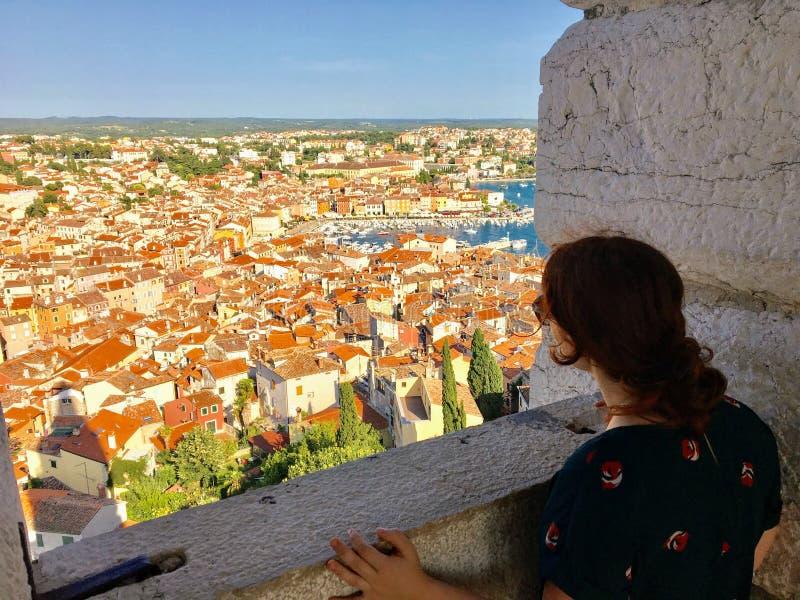 Seule une jeune femme se tenant du haut d'une vieille tour de cloche en pierre regardant la belle vieille ville de Rovinj, Croati photographie stock libre de droits