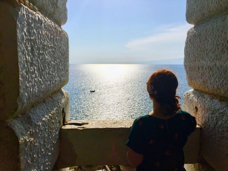 Seule une jeune femme se tenant du haut d'une vieille tour de cloche en pierre regardant le vaste océan image stock