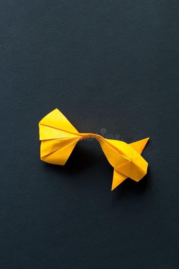 Seulement or fait main simple d'origami de métier de papier ou poissons jaunes de carpe de koi sur le fond noir Vue supérieure, p photo stock