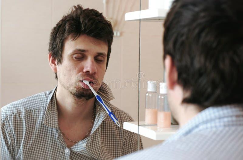 Seulement homme de réveil somnolent torturé devant le miroir avec une brosse à dents dans sa bouche image libre de droits