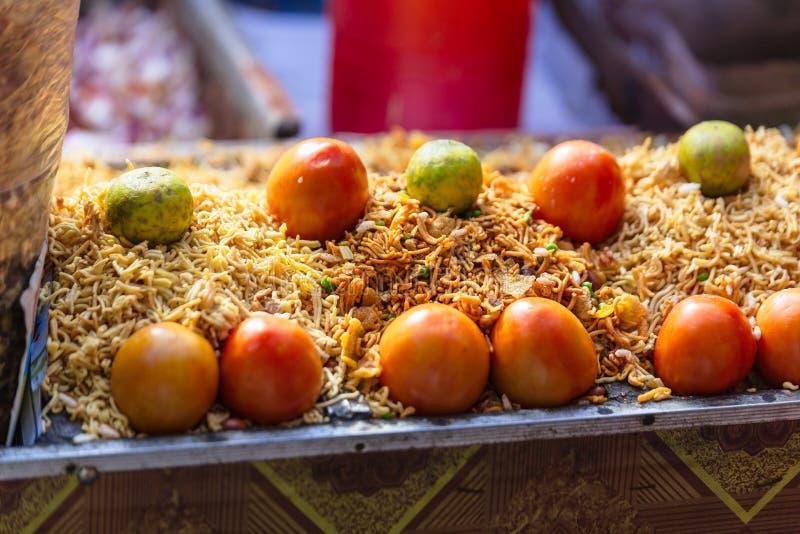 Sev med tomaten och limefrukt är en populär indisk mellanmålmat som består av små stycken av frasiga nudlar arkivbilder