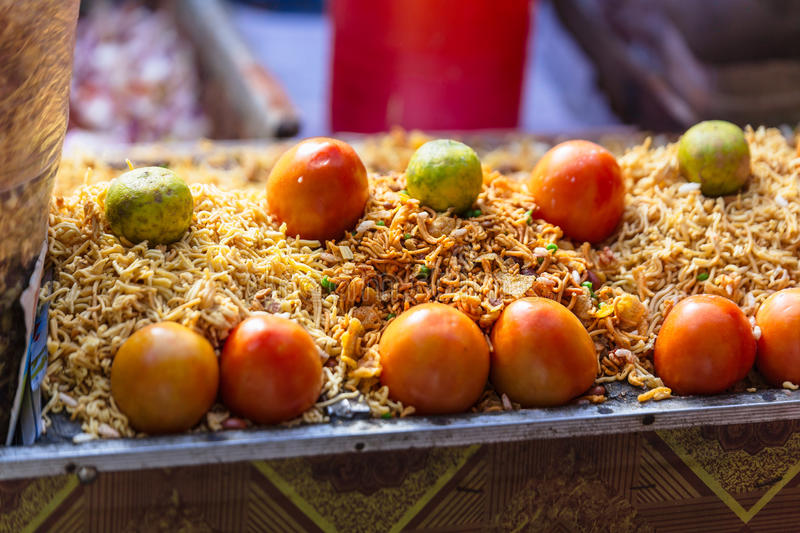 Sev with tomato and lime is a popular Indian snack food consisting of small pieces of crunchy noodles. stock images