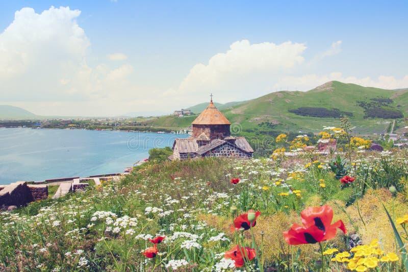 Sevanavank在亚美尼亚观光 塞凡湖、绿色山和天空看法  与黄色和白花的开花的领域 免版税库存图片