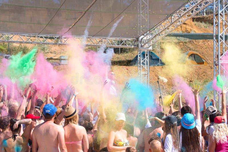 Sevastopol Krim: Lycklig folkdans under det färgrika pulvermolnet på holifestivalen av färger i sommar arkivbilder