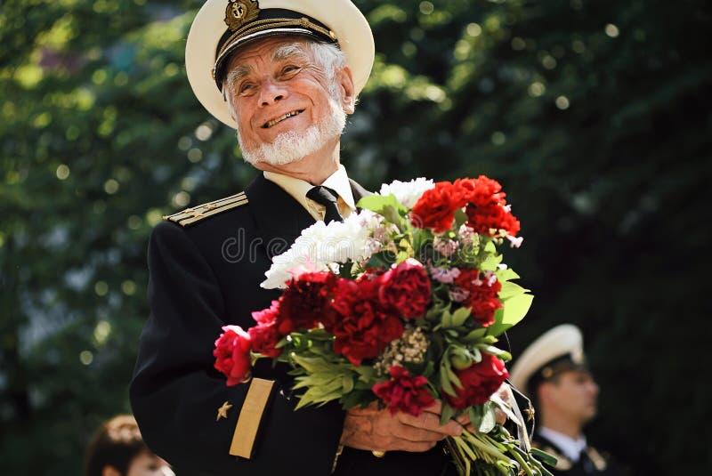 Sevastopol, Ukraina - 9 maj 2012: Joyful, leende andra veteran från andra världskriget med blommor vid paraden under firandet av  royaltyfri bild