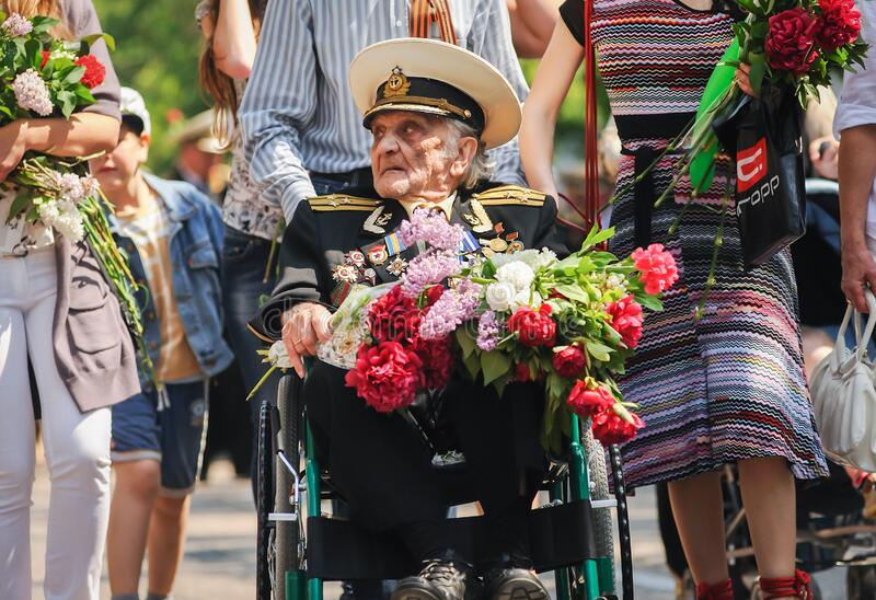 Sevastopol, Ukraine - May 9, 2012: an old World War II veteran in a wheelchair with flowers at the parade during the celebration o. F `Victory Day` over Nazi royalty free stock image